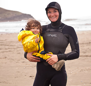 Child and mother in wet suit on a beach near Tofino